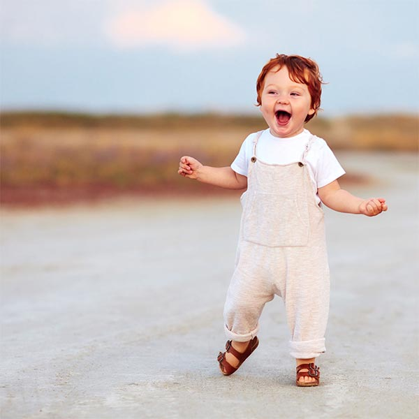 image of young baby walking and smiling