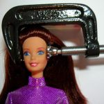image of Barbie with vice grip on her head