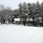 image of snow covered street and home